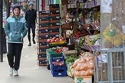 © Licensed to London News Pictures. 25/12/2020. London, UK. A woman walks past a fruit and vegetable shop in north London, which is open on Christmas Day. Photo credit: Dinendra Haria/LNP