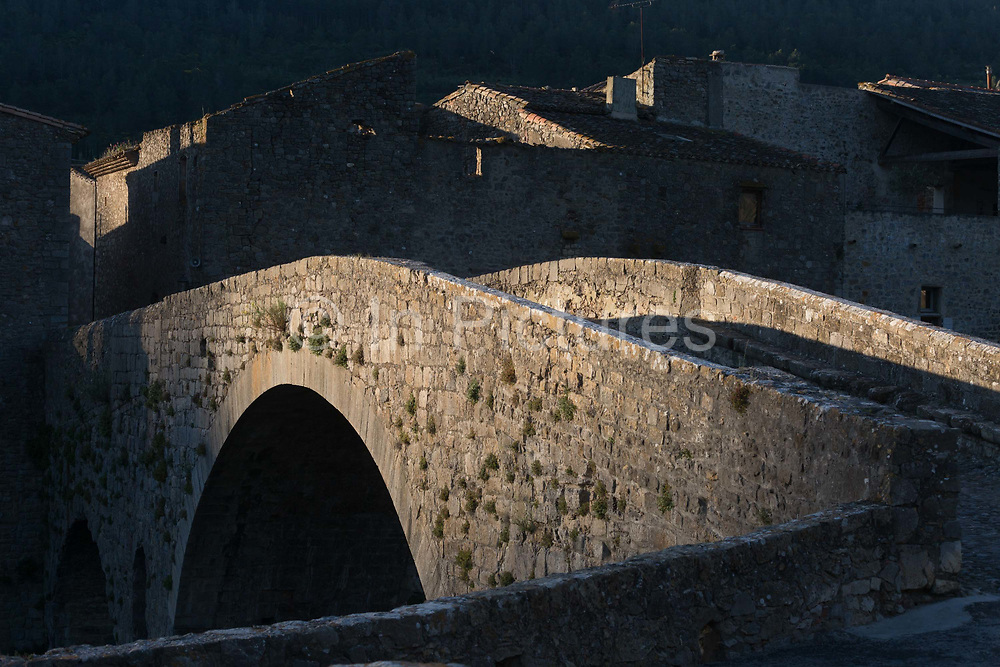 Dawn light on the stone hump-backed bridge in the pretty medieval walled village of Lagrasse, on 23rd May, 2017, in Lagrasse, Languedoc-Rousillon, south of France. Lagrasse is listed as one of Frances most beautiful villages and lies on the famous Route 20 wine route in the Basses-Corbieres region dating to the 13th century.