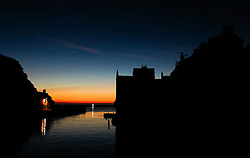 © Licensed to London News Pictures.02/10/15<br /> Staithes, UK. <br /> <br /> Dawn breaks over the harbour in the North Yorkshire village of Staithes on the east coast as the warm autumn weather continues.<br /> <br /> Photo credit : Ian Forsyth/LNP