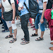 Refugees and immigrants waiting in the queue to board to the Coast Guard's bus that will transport them from Molyvos to one of the camps in Mytiline.