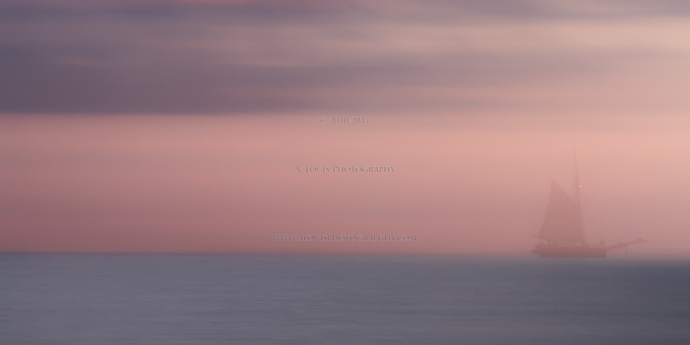Blurred Impression-  A sailing ship fades into the horizon after sunset