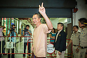 """23 JANUARY 2013 - BANGKOK, THAILAND:   SOMYOT PRUESAKASEMUK waves the """"V for Victory"""" as he walks into Bangkok Criminal Court followed by court security Wednesday. Somyot was sentenced to 11 years imprisonment Wednesday for violations of Thailand's """"Lese Majeste"""" laws. He was arrested on April 30, 2011, and charged under article 112 of Thailand's penal code, which states that ?whoever defames, insults or threatens the King, the Queen, the Heir-apparent or the Regent, shall be punished with imprisonment of three to fifteen years"""" after the magazine he edited, """"Red Power"""" (later changed to """"The Voice of Thaksin"""") published two articles by Jit Pollachan, the pseudonym of Jakrapob Penkair, the exiled former spokesman of exiled fugitive former Prime Minister Thaksin Shinawatra. Jakrapob, now living in Cambodia, has never been charged with any crime for what he wrote.     PHOTO BY JACK KURTZ"""