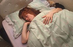 Teenage girl sleeping in bed,