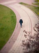 A tilt shift view of a person walking along a brick walkway in a park. Missoula Photographer, Missoula Photographers, Montana Pictures, Montana Photos, Photos of Montana