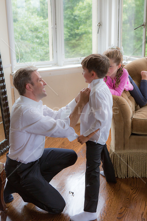 father helping a child dress for a formal occasion