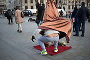 Yoda street performer takes a break from his levitation suit in Trafalgar Square, London, UK. In this area there are approximately four Yodas in a line all touting for money from passing tourists. Occasionally they let their guard and trick slip as they climb out of their costume.
