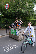 A young cyslist passes through the barriers that form an LTN Low Traffic Neighbourhood, an experimental closure by Southwark Council preventing motorists from accessing the junction of Carlton Avenue and Dulwich Village. Restrictions also prevent traffic from passing through at morning and afternoon rush-hour times in the borough of Southwark, on 14th June 2021, in London, England.