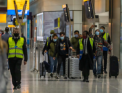 © Licensed to London News Pictures. 16/02/2021. London, UK. Officials escort passengers through Terminal 5 and into white coaches at London Heathrow this morning as quarantine hotels near Heathrow start to fill up with travellers from red list countries. From yesterday, (Monday 15 February 2021) anyone arriving from a red-list destination must quarantine at a designated hotel and pay a hotel fee of £1,750 for a 10 day quarantine period. Photo credit: Alex Lentati/LNP