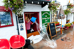 © Licensed to London News Pictures. 26/10/2019. Crickhowell, Powys, Wales, UK. Water is bailed out of The Bridge End Inn in Crickhowell as rain falls relentlessly and the level of the river Usk rises dramatically. Water enters The Bridge End Inn basement in Bridge Street, Crickhowell  in Powys. Photo credit: Graham M. Lawrence/LNP