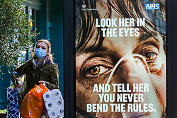 "© Licensed to London News Pictures. 29/01/2021. London, UK. A shopper wearing a protective face covering walks past the government's 'Look her in the eyes - And tell her you never bend the rules. ' publicity campaign poster in north London. Covid-19 infection rates are continuing to drop across London. But health experts are warning Londoners to follow the lockdown rules, as ""any relaxation would risk a rapid reversal or decline."" Photo credit: Dinendra Haria/LNP"