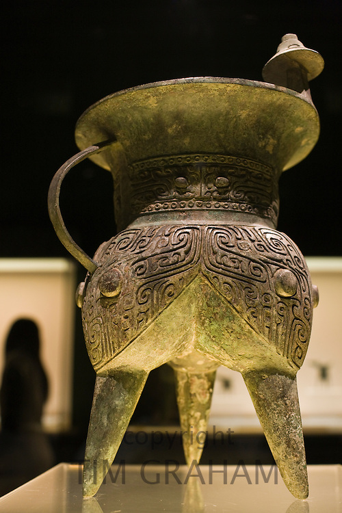 Bronze wine vessel in the shape of an animal mask, on display in glass case at the Shanghai Museum, China