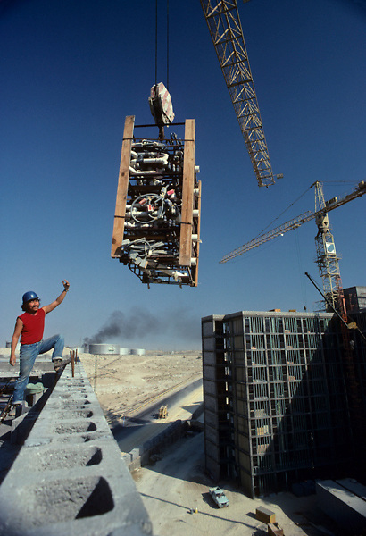 Construction in Saudi Arabia with oil tank farm in background.