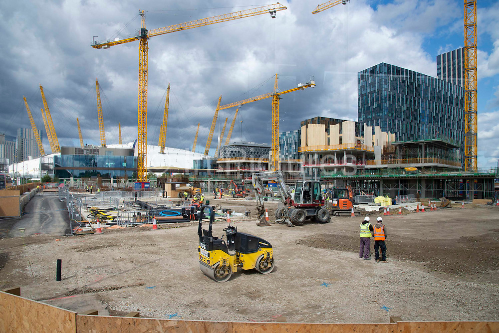 Yellow cranes blend with yellow girders of the O2 arena as on going construction work continues at the Design District site in Greenwich Peninsula in London, United Kingdom on 15th August , 2019. Scheduled to fully open in 2020, developers Knight Dragon Developments Ltd aim to deliver 15,000 new homes. 13,000 new jobs. 7 new neighbourhoods.