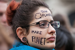 London, UK. 1st December, 2018. An environmental campaigner with a painted face takes part in the Together for Climate Justice demonstration in protest against Government policies in relation to climate change, including Heathrow expansion and fracking. Following a rally outside the Polish embassy, chosen to highlight the UN's Katowice Climate Change Conference which begins tomorrow, protesters marched to Downing Street.