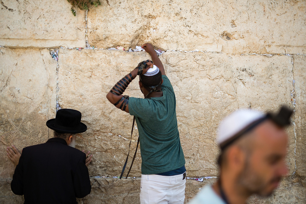A Jewish man (C) puts a note containing a prayers or a messages in the cracks between the stones of the Western Wall, Judaism's holiest prayer site, in the Old City of Jerusalem, Israel, on September 17, 2017.