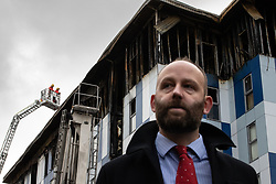 """© Licensed to London News Pictures. 16/11/2019. Bolton, UK. PAUL DENNETT of Greater Manchester's High Rise Taskforce at a the site of the blaze . Firefighters work at the scene where a fire broke out overnight (15th/16th November 2019) at a block of flats known as """" The Cube """" , in Bolton Town Centre . At least two people are known to have been treated by paramedics at the scene of the six-story block , which is occupied by students of the University of Bolton . Photo credit: Joel Goodman/LNP"""