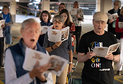 © Licensed to London News Pictures. 23/06/2021. Epsom, UK. Members of Epsom Choral Society rehearse in a multi-storey car park in Epsom, Surrey. The choir, in it's 99th year, has resorted to rehearsing in a socially distanced way on the 4th floor of the Ashley Shopping Centre car park after government Covid-19 regulations were updated to say that amateur choirs are only allowed to gather in groups of six indoors. Epsom and Ewell Borough Council agreed to the use of the car park which allows the choral society to rehearse in two groups of 30 outdoors but sheltered from the elements. Photo credit: Peter Macdiarmid/LNP