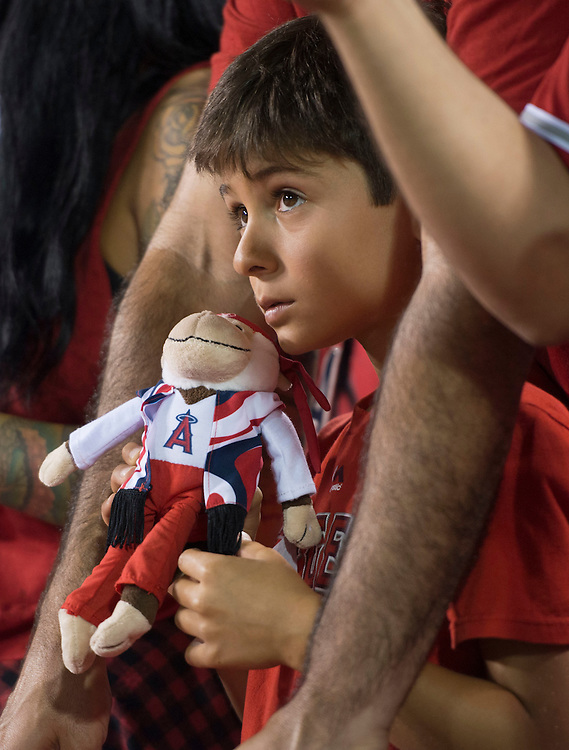 The young fan holds his 70's Rally Monkey while looking for baseballs after the game at Angel Stadium on Friday.<br /> <br /> ///ADDITIONAL INFO:   <br /> <br /> angels.0716.kjs  ---  Photo by KEVIN SULLIVAN / Orange County Register  -- 7/15/16<br /> <br /> The Los Angeles Angels take on the Chicago White Sox at Angel Stadium.