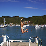 A teenage girl jumps into the water from a pier at Waikawa Bay near Picton.  Waikawa is the home of New Zealand's 3rd largest Marina only minutes away from  Queen Charlotte Sounds near Picton at the top of the South Island of New Zealand,  28th January 2011. Photo Tim Clayton.