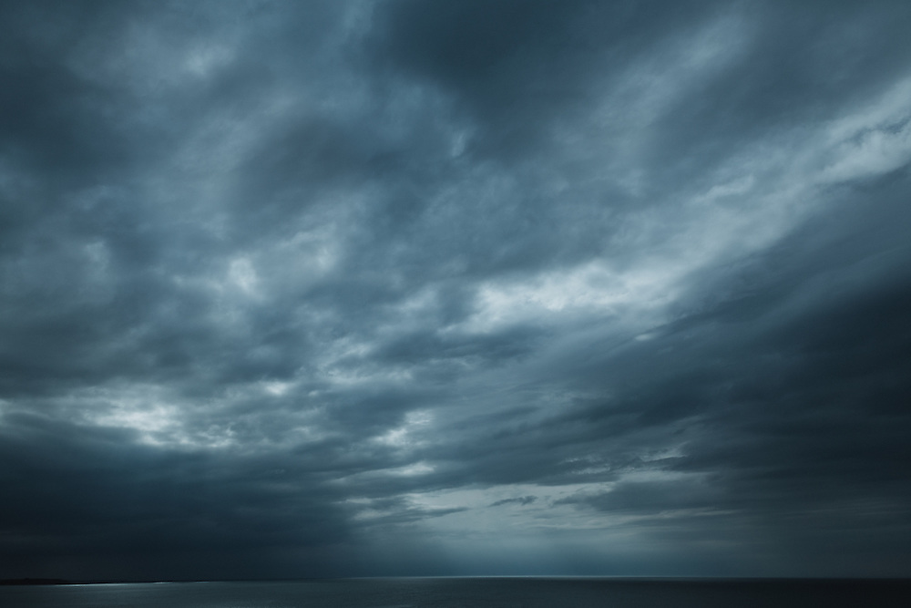 Dramatic skies over the sea viewed from the Pointe du Grouin, Brittany, France.