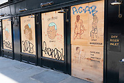 Explicit graffiti outside a boarded up bar on Old Compton Street in Soho under coronavirus lockdown on 26th June 2020 in London, England, United Kingdom. As the July deadline approaces and government will relax its lockdown rules further, the West End remains quiet, while some non-essential shops are allowed to open with individual shops setting up social distancing systems.