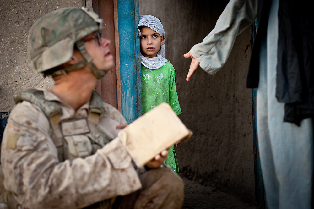 Corporal Michael Dutcher, 22, from Asheville, North Carolina, takes biometric data from Afghan villagers with a device called a BAT-HIDE. Dutcher was killed by an IED several weeks after this picture was taken.