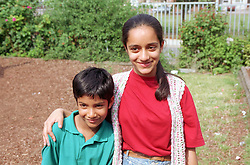 Young girl standing in garden with arm around younger brother,