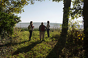 Three country walking women admire the beauty of a field of flax, on 21st October 2018, in Hollingbourne, Kent, England.