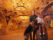Winemaker Daryl Sattui, with his son Mario and dog Lupo, in one of the many underground wine storage rooms of a castle being built in the Napa Valley, California..Daryl Sattui's Castello di Amoroso, a version of a Tuscan hilltop castle in Calistoga, California. Under construction in 2003.  MODEL RELEASED.
