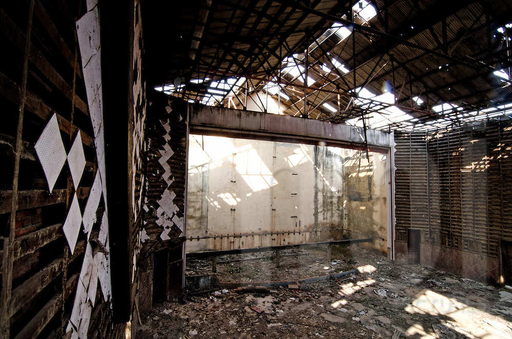 Abandoned Sengchaleun cinema, Savannakhet, Laos, Asia. Interiors are in complete decay and very messy. Roof structure is rusty and full of trash lay on the ground of the projection room.