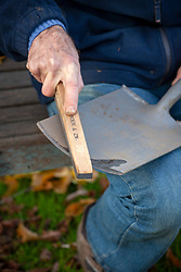 Sharpening a spade using a tool sharpener and oil
