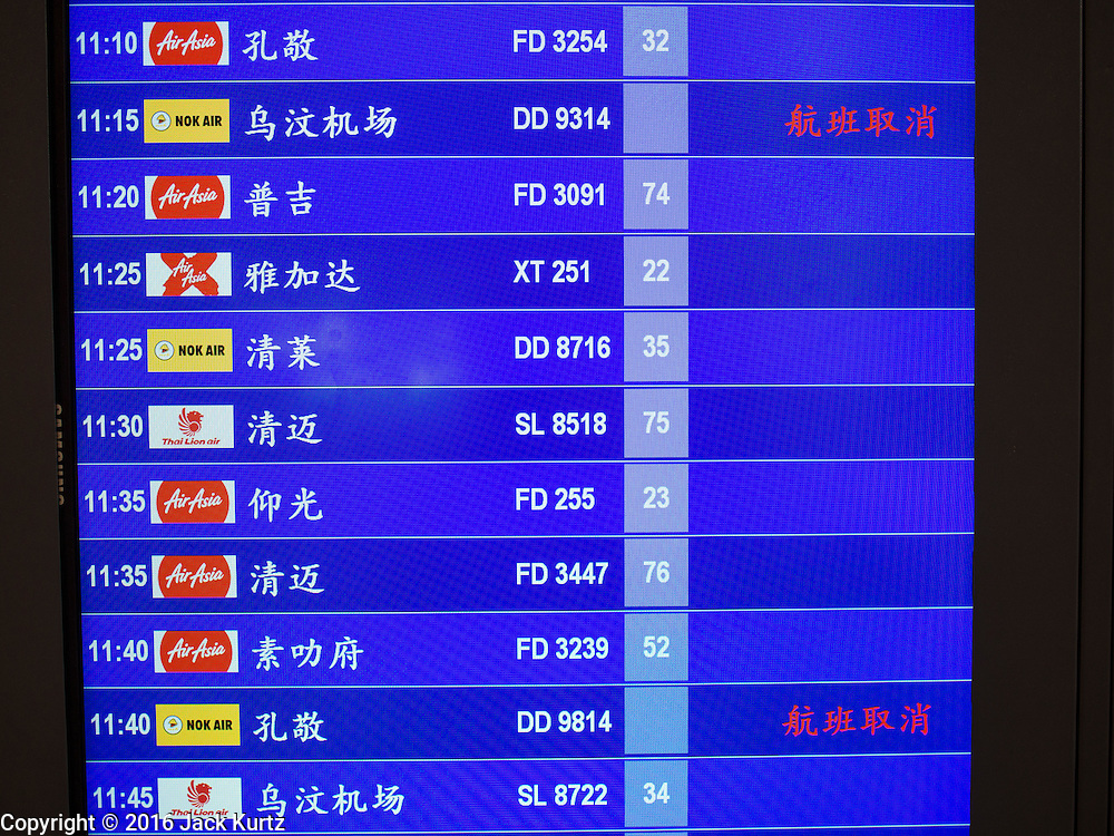 """23 FEBRUARY 2016 - BANGKOK, THAILAND:  A flight status board in Chinese, because of the large number of Chinese tourists coming to Thailand, at Don Mueang International Airport shows some of the cancellations of Nor Air flights. Nok Air, partly owned by Thai Airways International and one of the largest and most successful budget airlines in Thailand, cancelled 20 flights Tuesday because of a shortage of pilots and announced that other flights would be cancelled or suspended through the weekend. The cancellations came after a wildcat strike by several pilots Sunday night cancelled flights and stranded more than a thousand travelers. The pilot shortage at Nok comes at a time when the Thai aviation industry is facing more scrutiny for maintenance and training of air and ground crews, record keeping, and the condition of Suvarnabhumi Airport, which although less than 10 years old is already over capacity, and facing maintenance issues related to runways and taxiways, some of which have developed cracks. The United States' Federal Aviation Administration late last year downgraded Thailand to a """"category 2"""" rating, which means its civil aviation authority is deficient in one or more critical areas or that the country lacks laws and regulations needed to oversee airlines in line with international standards.        PHOTO BY JACK KURTZ"""