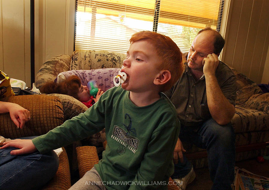 A tired John Bennett shuts his eyes briefly after starting work at 4 a.m. Hunter keeps an eye on his mom, Alicia, while Ciara rests on the couch. February  23, 2004