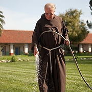 Fr. Larry Gosselin,.O.F.M. tends to his flowers outside his room where he resides at teh Mission San Miguel.