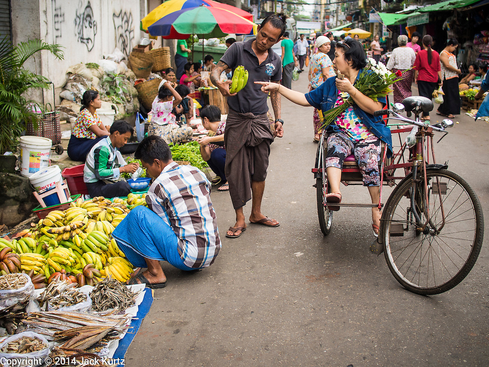 02 NOVEMBER 2014 - YANGON, MYANMAR: A vendor shows a woman in a trishaw (a bicycle powered rickshaw) bananas in the 38th Street morning market in downtown Yangon, Myanmar. The market is typical of morning markets in Yangon, a city coming out of more the 50 years of economic isolation. Most people still shop in markets because Yangon does not have as many grocery stores as Bangkok, Kuala Lumpur or many other large cities.     PHOTO BY JACK KURTZ