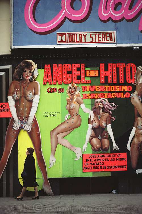 Woman walking under a strip club billboard in Madrid, Spain.