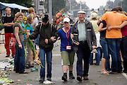 Nederland, Nijmegen, 20-7-2007..Vierdaagse, Tijdens de intocht brak rond half twee op de St Annastraat, via gladiola,een stortbui met onweer uit. Ondanks het slechte weer blijven de lopers doorgaan, met de finish in zicht. Hier komt een van de laatste lopers met hulp van familie over de St Annastraat, terwijl studenten op straat hun feestje vieren...Foto: Flip Franssen/Hollandse Hoogte
