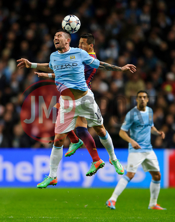 Man City Defender Aleksandar Kolarov (SRB) and Barcelona Forward Alexis Sanchez (CHI) compete in the air - Photo mandatory by-line: Rogan Thomson/JMP - Tel: 07966 386802 - 18/02/2014 - SPORT - FOOTBALL - Etihad Stadium, Manchester - Manchester City v Barcelona - UEFA Champions League, Round of 16, First leg.