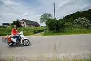 In het buitengebied van Waddinxveen rijdt een postbesteller van PostNL zijn ronde langs de boerderijen op een brommer.<br /> <br /> In Waddinxveen a postman is making his round on a moped, passing the farms.