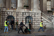 People, tourists and workmen go about their business as amazing light bounces off a building onto a corner in the City of London, UK.