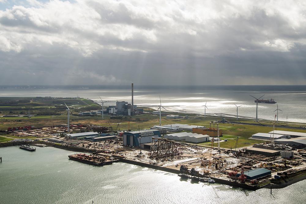 Nederland, Zeeland, Borssele, 23-10-2013; energielandschap met zonnestralen door het wolkendek, die het Industrieterrein Vlissingen-Oost verlichten. met oa. COVRA (Centrale Organisatie Voor Radioactief Afval) - het oranje gebouw, een bedrijf dat zorgt voor de opslag van licht radioactief materiaal.<br /> Binnenvaartschip vaart langs.<br /> Industrial area and power plant Borsele with COVRA, a company that handles the storage of radioactive waste<br /> luchtfoto (toeslag op standaard tarieven);<br /> aerial photo (additional fee required);<br /> copyright foto/photo Siebe Swart.