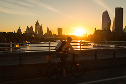 © Licensed to London News Pictures. 24/09/2018. London, UK. A cyclist on Waterloo Bridge during sunrise on the River Thames during cold but sunny weather this morning.  Photo credit: Vickie Flores/LNP