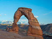 View of Delicate Arch in a cloud shadow with the La Sal Mountains in the background, nearing sunset; Arches National Park, Moab, Utah, USA.