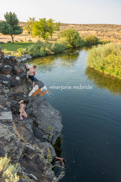 Teens jumping from cliffs at the Ledges swimming hole in Richfield, Idaho.