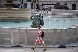 © Licensed to London News Pictures. 12/06/2021. London, UK. A woman walks past a newly installed barrier around a fountain. Work continues on the construction of a new Fan Zone at Trafalgar Square in central London ahead England's opening fixture in the 2020 UEFA European Football Championship tomorrow. Fans will be able to watch England games on a giant screen in the centre of the capital. Photo credit: Ben Cawthra/LNP