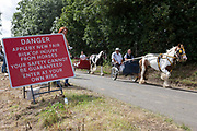 With a red danger sign in the foreground, two horses and wagons are driven down the flash, a strip of dirt road where people show off their horses at Appleby Horse Fair, the biggest gathering of Gypsies and travellers in Europe, on 14th August, 2021 in Appleby, United Kingdom. Appleby Horse Fair attracts thousands from Gypsy, Romany, and traveller communities annually, making it the biggest gathering of its kind in Europe. Generally held for a week every June, the fair was postponed in 2020 and pushed forward to August in 2021 due to Coronavirus.