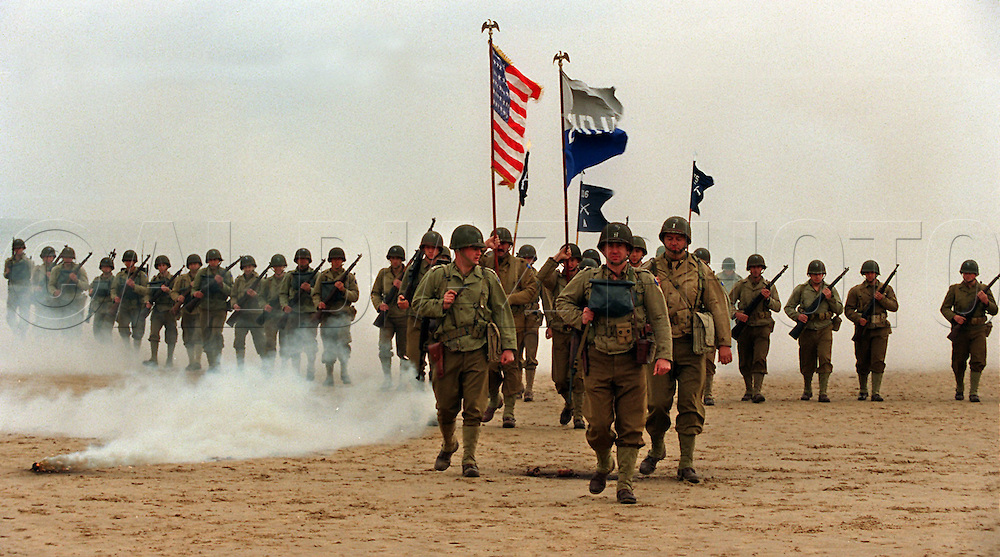 French re-enactors of the US Armies, 29th Infantry Division, march onto Omaha Beach, Normandy France, during ceremonies for the 50th anniversary of D-Day.