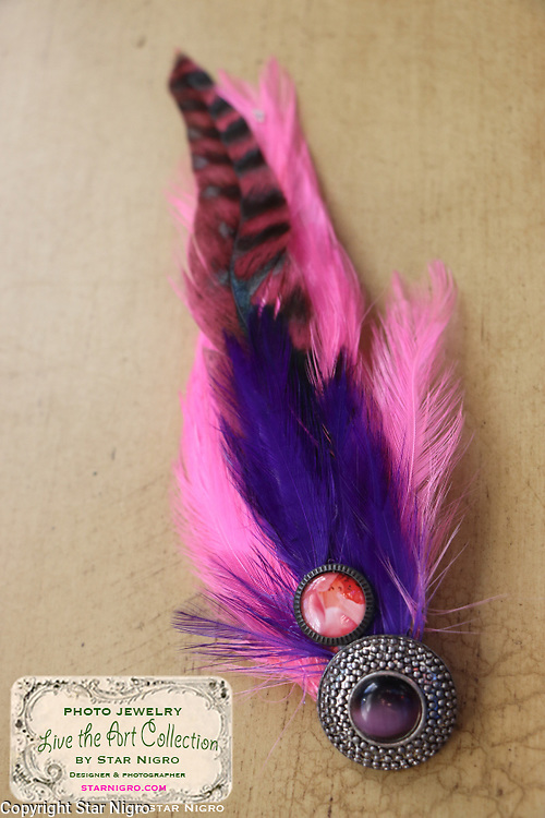 """Rose photo fascinator with vibrant feathers handmade with love by Star Nigro<br /> <br /> This handcrafted wearable art piece can also be clipped to a blouse,pocket book,hat etc. <br /> <br /> Materials: rose photo,pink & purple colored feathers,with purple glass accent, barrette clip<br /> <br /> size: 2"""" x 7"""" x1/4""""<br /> <br /> price: $52.00<br /> <br /> <br /> + Giveback<br /> When you make a purchase from this site will be shared with a non-profit that focuses on making a positive difference in the world today.<br /> <br /> Buying art  + Making a difference = Art with Heart<br /> <br /> photo by Star Nigro<br /> <br /> StarNigro.com<br /> <br /> ©2021 All artwork is the property of STAR NIGRO.  Reproduction is strictly prohibited."""