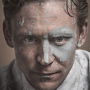 """Portrait of Tom Hiddleston as Dr Robert Laing in High Rise. <br /> Ben Wheatley's High Rise, the film adapted from J.G. Ballard's novel about the structure of a capitalistic society found within one high rise apartment building. Tom Hiddleston stars as the man who runs the whole thing. The cast includes Luke Evans, Sienna Miller, Jeremy Irons, James Purefoy, Elisabeth Moss, and Keeley Hawes.<br /> <br /> High-Rise is directed by British filmmaker Ben Wheatley (Down Terrace, Kill List, Sightseers, A Field in England), from legendary producer Jeremy Thomas (The Last Emperor, Sexy Beast, A Dangerous Method, 13 Assassins, Kon-Tiki, Only Lovers Left Alive), and written by Amy Jump (Kill List, A Field in England). It's based on J.G. Ballard's acclaimed 1975 novel of the same name: """"When a class war erupts inside a luxurious apartment block, modern elevators become violent battlegrounds and cocktail parties degenerate into marauding attacks on 'enemy' floors."""" The film first premiered at the Cannes Film Festival, and also played London and Fantastic Fest this year."""