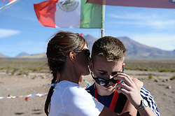 © Licensed to London News Pictures. 14/11/2013.<br /> <br /> British mother and son pair Yvonne & Connor brown, bibs no. 6 &5.<br /> <br /> Inaugural Volcano Marathon, Atacama Desert, Chile. The race took place in the Atacama Desert in Chile, beginning at an altitude of 4,400 metres (14,500 feet) in the vicinity of Lascar Volcano. It was a gruelling affair for many of the competitors who had to encounter some challenging hills and manage the impact of the heat and oxygen deprivation. The average altitude of the entire race was close to 4,000 metres and temperatures reached the mid 20s Celsius, or almost 80 Degrees Farenheit.<br /> <br /> Photo credit : Mike King/LNP<br /> <br /> Further information and link to video here: https://www.dropbox.com/s/0277bepxvo0t8il/Marathon%20copy.txt